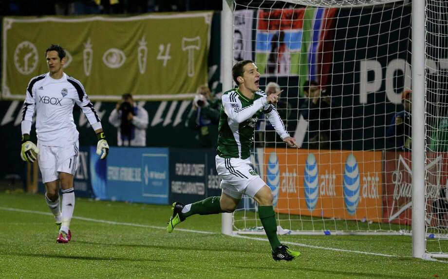 Portland Timbers' Will Johnson, right, celebrates after he scored a goal on Seattle Sounders goalkeeper Michael Gspurning, left, on a penalty kick in the first half of the second game of the Western Conference semifinals in the MLS Cup soccer playoffs, Thursday, Nov. 7, 2013, in Portland, Ore. Photo: Ted S. Warren, AP / AP