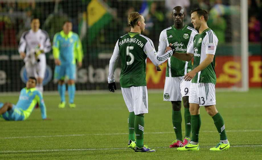 Portland Timbers' Michael Harrington (5) Mamadou Danso, second from right, and Jack Jewsbury, right, celebrate the Timbers 3-2 win over the Seattle Sounders in the second half of the second game of the Western Conference semifinals in the MLS Cup soccer playoffs, Thursday, Nov. 7, 2013, in Portland, Ore. The win gave the Timbers a 5-3 aggregate score in the two-match series and the Timbers will to the Western Conference semifinals against Real Salt Lake. Photo: Ted S. Warren, AP / AP