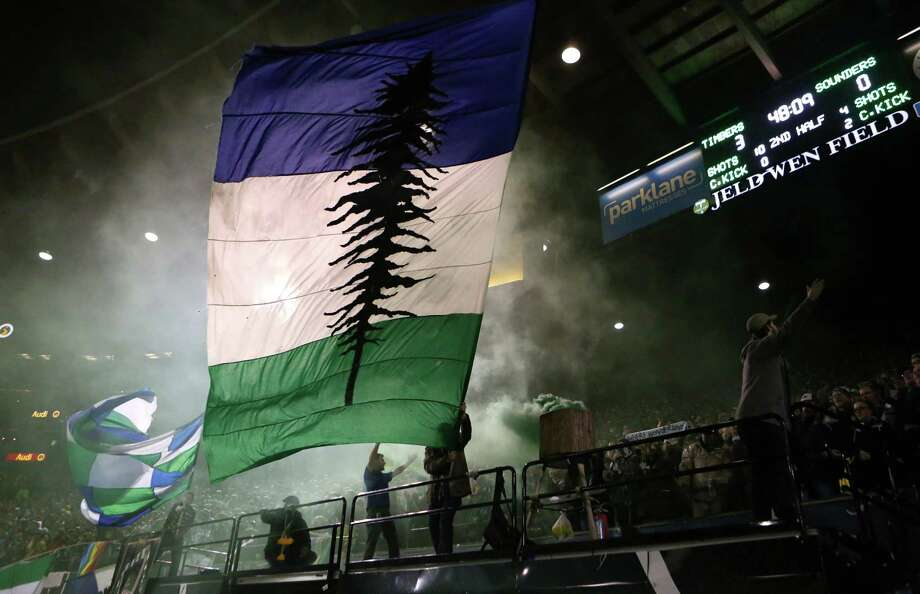Smoke and flags fly from the Timbers Army as the Timbers score against the Seattle Sounders during an MLS Playoff match at JELD-WEN Field in Portland on Thursday, November 7, 2013. The Timbers defeated the Sounders, ending the season for Seattle. Photo: JOSHUA TRUJILLO, SEATTLEPI.COM / SEATTLEPI.COM