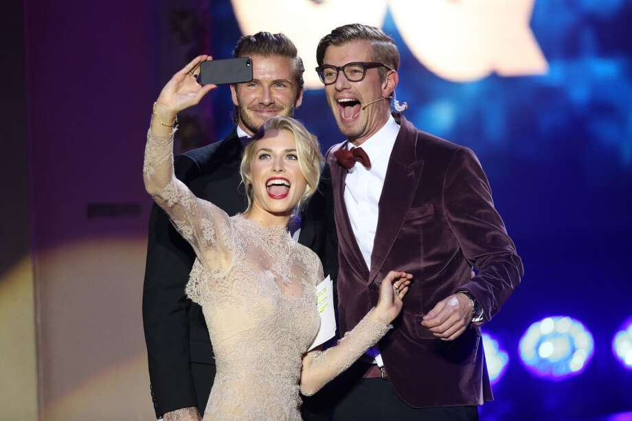 Lena Gercke takes a picture of David Beckham (L), Joko Winterscheidt and herself on stage at the GQ Men Of The Year Award at Komische Oper on November 7, 2013 in Berlin, Germany.  (Photo by Sean Gallup/Getty Images  for GQ) Photo: Sean Gallup