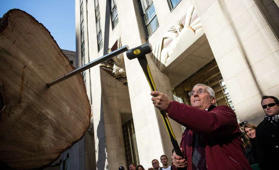 NEW YORK, NY - NOVEMBER 08:  John Vargoshe hammers a piston into a 76-foot tall Norway Spruce, which came from his front lawn in Shelton, CT, while the tree is prepared to be the 2013 Rockefeller Center Christmas Tree on November 8, 2013 in New York City.  The tree comes from the Vargoshe family' front lawn, it was likely planted in the 1950s.  (Photo by Andrew Burton/Getty Images) ORG XMIT: 187493731 Photo: Andrew Burton, Getty / 2013 Getty Images