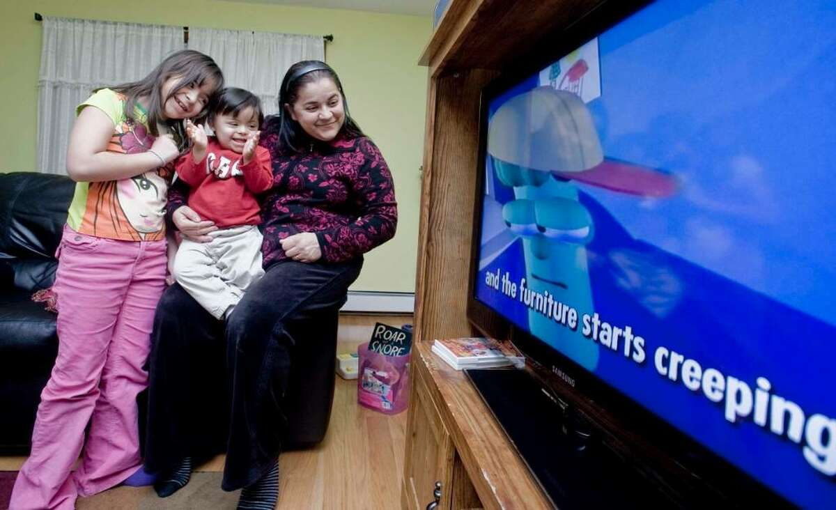 Deborah Ferreira, 7, brother Philip, 2 and mom Elaine Ferreira watching a video at their home in Danbury. Philip has Down syndrome. Thursday, Jan. 21, 2010