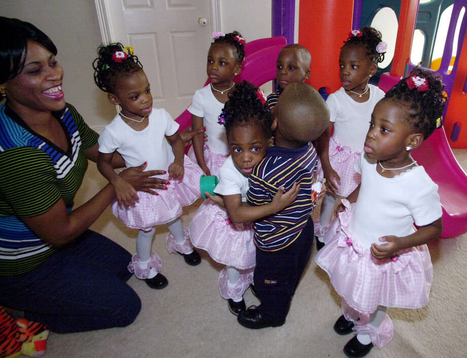 Nkem Chukwu, left, gathers her seven children Chidi, Gorom, Ikem, center rear, Chima and Ebuka, as Echerem, front left, and Jioke hug as the seven celebrate their third birthday Thursday, Dec. 20, 2001, at their home in League City, Texas. Photo: PAT SULLIVAN, AP / AP