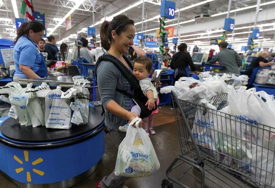 In this Wednesday, Nov. 22, 2012, photo, Eva Cevallos with her eleven-month daughter, Quinn, shop during the Thanksgiving Pre-Black Friday event at the Walmart Supercenter store in Rosemead, Calif. Wal-Mart Stores Inc. offered a weak business outlook Thursday, Feb. 21, 2013,  as new economic challenges for its low-income U.S. shoppers start to take a toll.  (AP Photo/Damian Dovarganes) Photo: Damian Dovarganes / AP