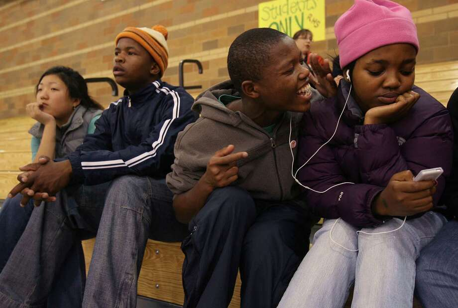 Friendship, high-school style. Pictured is Roosevelt exchange student Beki Boneni serenading student Nosimphiwe Ncoko in 2006 during a basketball game, while students Alice Seo (far left) and Athabile Teto watch the game.  Photo: Mike Urban, Seattle Post-Intelligencer File / Seattle Post-Intelligencer