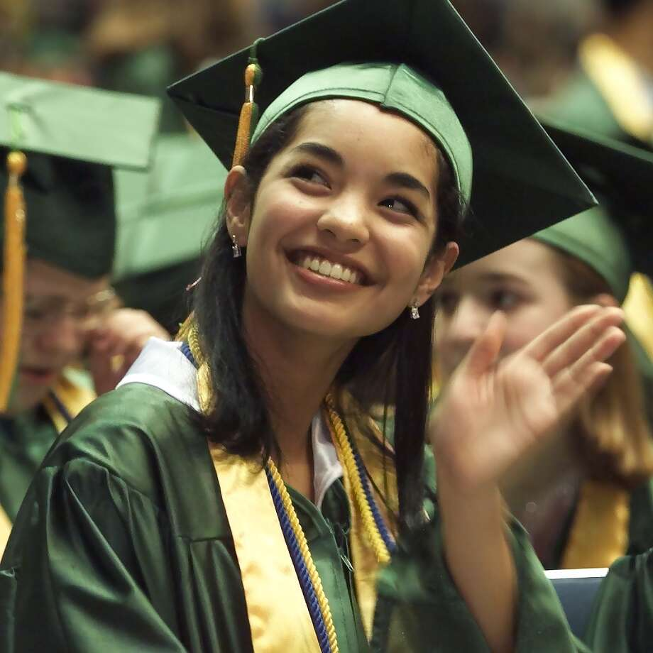 Janelle Velasquez waves to her family during Roosevelt's graduation ceremony at Mercer Arena in 2000.  Photo: MIKE URBAN, Seattle Post-Intelligencer File