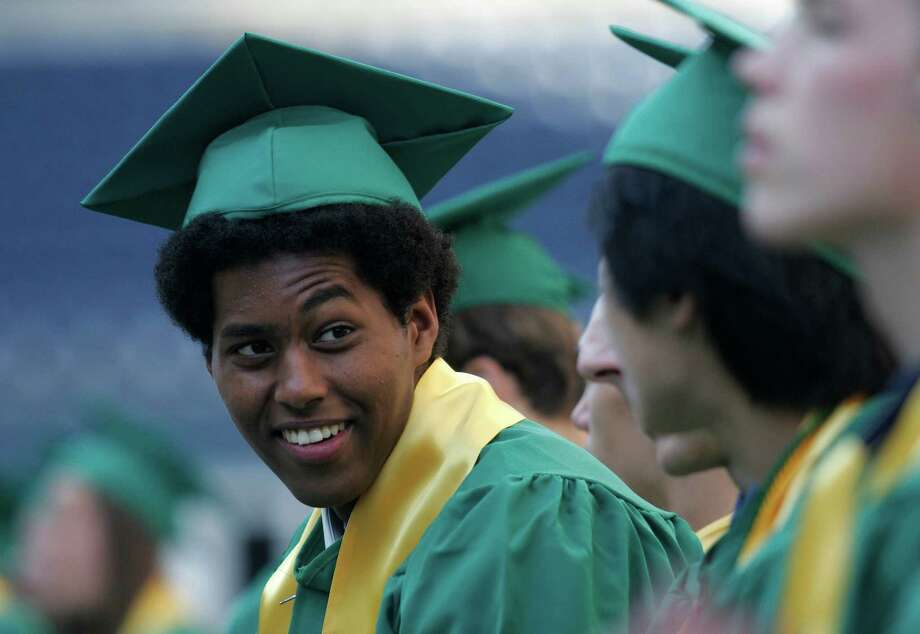 Roosevelt class of 2000 grad Thomas Gee shares a look with classmates during their graduation ceremony at at Qwest Field on June 20, 2005.  Photo: NIKI DESAUTELS, Seattle Post-Intelligencer File
