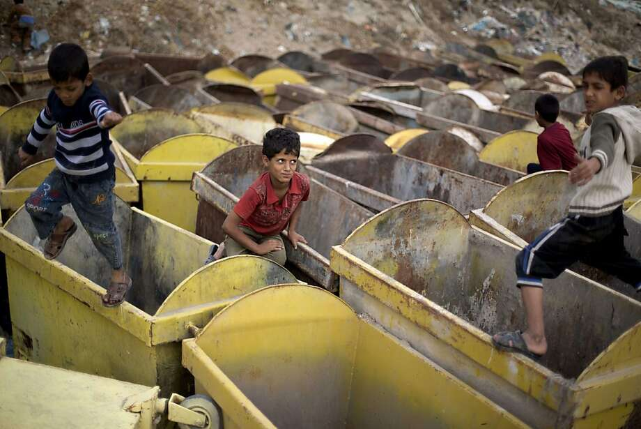 The boys in the bins: Palestinian youths play among old trash containers next to a flea market in Gaza City. Photo: Mohammed Abed, AFP/Getty Images
