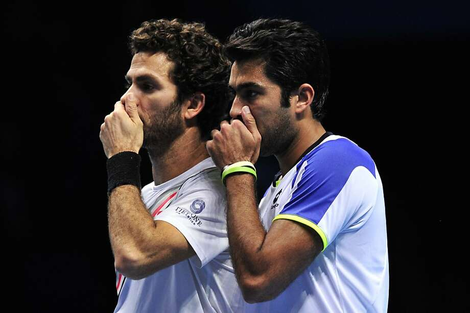 Psst, I'm fresh out of ideas. You? Pakistan's Aisam-Ul-Haq Qureshi (right) and his partner, Netherlands' Jean-Julien Rojer, cover their mouths so their opponents, the American Bryan brothers, can't lip-read their strategy at the ATP World Tour Finals in London. Not that it mattered. The Bryans won anyway, 7-6, 1-6, 14-12. Photo: Glyn Kirk, AFP/Getty Images