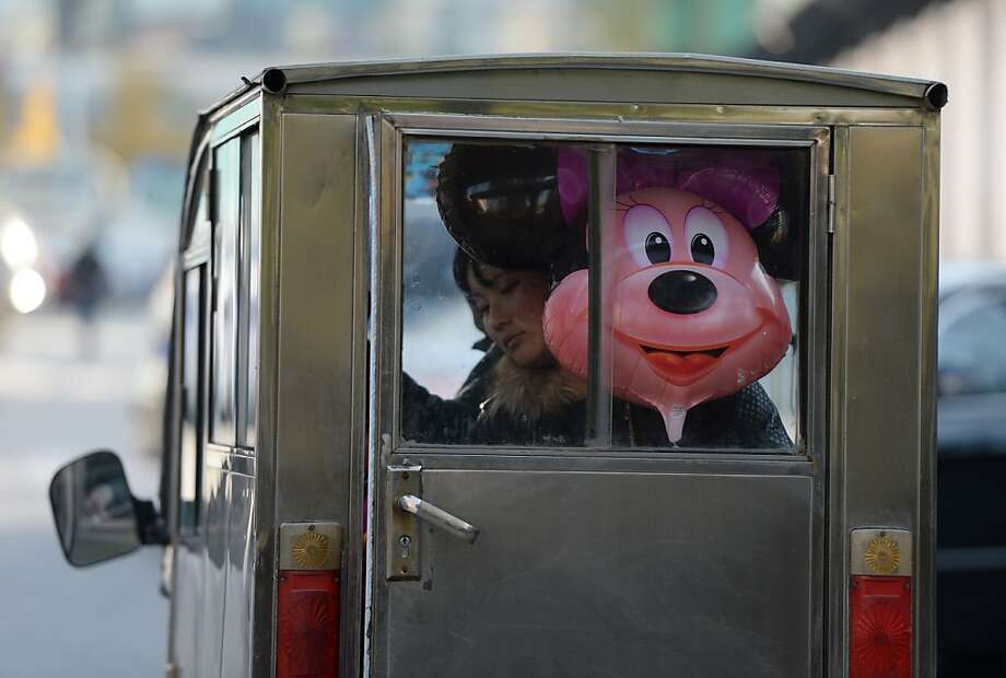 It's a small world after all:A woman rides a Minnie taxi in Beijing. Photo: Mark Ralston, AFP/Getty Images