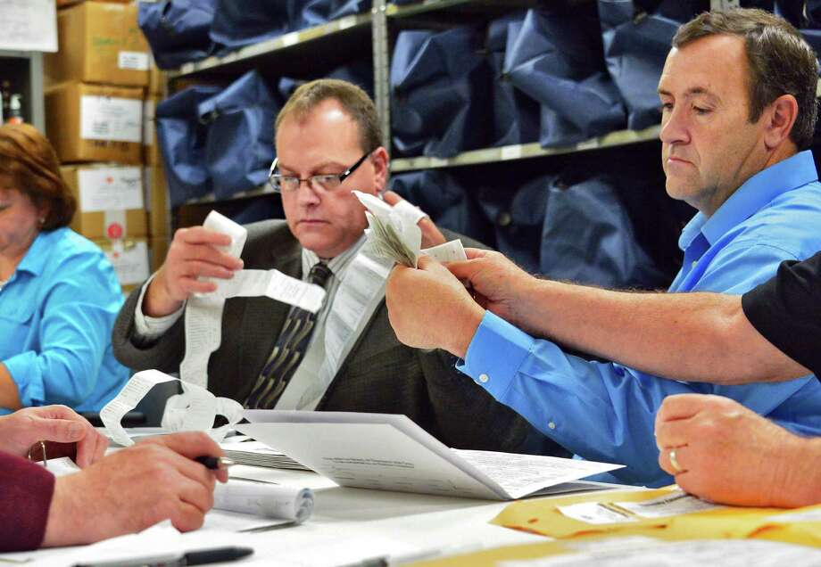 County election commissioners Ed McDonough and Larry Bugbee, at right, as Rensselaer County Board of Elections counts absentee ballots in Troy's at-large council race at the Rensselaer County Office Building on Friday, Nov. 8, 2013, in Troy, NY.  (John Carl D'Annibale / Times Union) Photo: John Carl D'Annibale / 00024560A