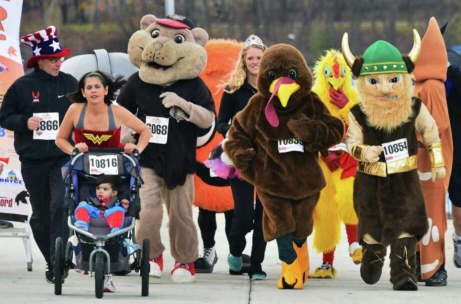 Costumed runners and regional mascots in a mini road race to promote the introduction of a costume contest in the 5K of this year's Troy Turkey Trot during a news conference in Riverfront Park Friday Nov. 8, 2013, in Troy, NY.  (John Carl D'Annibale / Times Union) Photo: John Carl D'Annibale / 00024577A