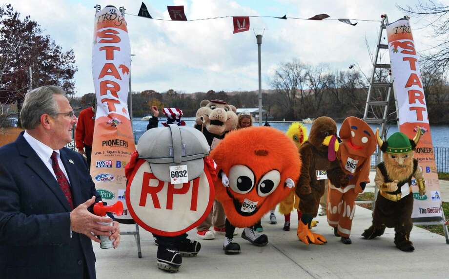 Mayor Lou Rosamilia, left, sounds a horn to start a mini road race of costumed runners and regional mascots to promote the introduction of a costume contest in the 5K of this year's Troy Turkey Trot during a news conference in Riverfront Park Friday Nov. 8, 2013, in Troy, NY.  (John Carl D'Annibale / Times Union) Photo: John Carl D'Annibale / 00024577A