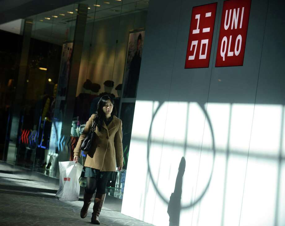 "Sherry Chiu, of Hamden, leaves UNIQLO's new Westfield Trumbull Mall store Friday, Nov. 8, 2013 after shopping their grand opening sale.  Chiu has shopped the New York City store location and said she is ""really excited that we have one in Connecticut now."" Photo: Autumn Driscoll / Connecticut Post"