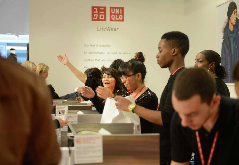 Gabrielle Cowett, of New Haven, beckons more customers to the checkout counter at UNIQLO's new Westfield Trumbull Mall store Friday, Nov. 8, 2013 during their grand opening sale. Photo: Autumn Driscoll / Connecticut Post