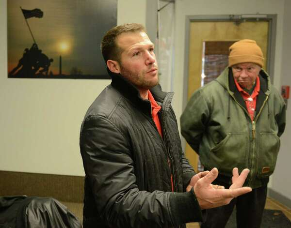 Dan Gaita, left, owner of Private Studio Fitness, talks with a group of veterans, including Bethel resident John Hogan, who served in Vietnam fr