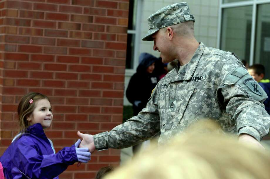 Second grade student Dakota Barcelos high fives Army Staff Sgt. Jeremy Payne, of Talladega, AL, Friday, Nov. 8, 2013 during a special visit to McKinley Elementary School for an assembly program honoring veterans. Photo: Autumn Driscoll / Connecticut Post