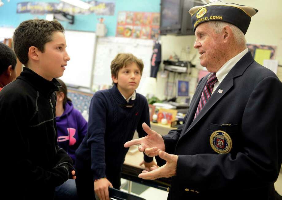 Fifth grade students Sean Rodriguez, left, and Giovanni Panagiotakis talk with World War II veteran Ed Crowley Friday, Nov. 8, 2013 during a special visit to McKinley Elementary School for an assembly program honoring veterans. Photo: Autumn Driscoll / Connecticut Post