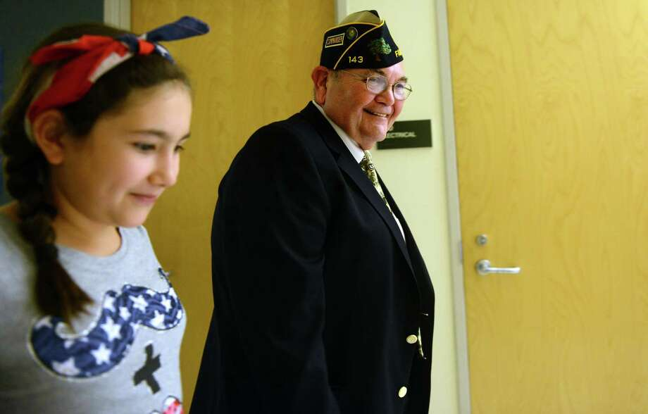 Fifth grade student Samantha Fahey walks with World War II veteran Tom Quinn Friday, Nov. 8, 2013 during a special visit to McKinley Elementary School for an assembly program honoring veterans. Photo: Autumn Driscoll / Connecticut Post