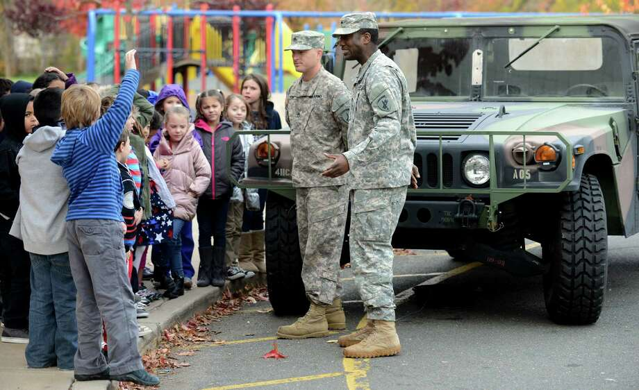 Army Staff Sgt. Jeremy Payne, of Talladega, AL, and Specialist Trevor King, of Bridgeport, talk with second grade students Friday, Nov. 8, 2013 during a special visit to McKinley Elementary School for an assembly program honoring veterans. Photo: Autumn Driscoll / Connecticut Post