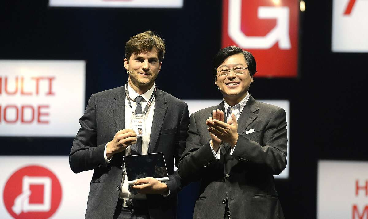 American actor Ashton Kutcher, left, stands with Lenovo's CEO Yang Yuanqing after they unveiled Lenovo's new Yoga tablet computer in Beijing, China, Friday, Nov. 1, 2013. Computer-maker Lenovo announced Wednesday, Oct. 30, 2013, it has hired tech-savvy actor Ashton Kutcher to help design and pitch its latest line of tablets, dubbing the Hollywood star a