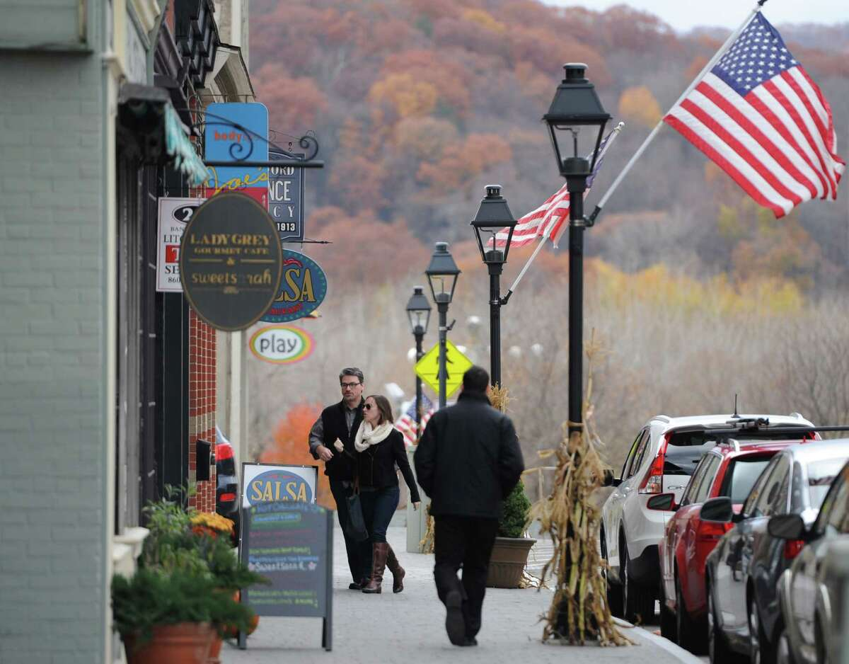 People walk down Bank Street in New Milford, Conn. on Friday, Nov. 8, 2013. New Milford is one of the most walkable towns in the area, ranking second out of 31 towns with a score of 88 according to Walkscore.com.