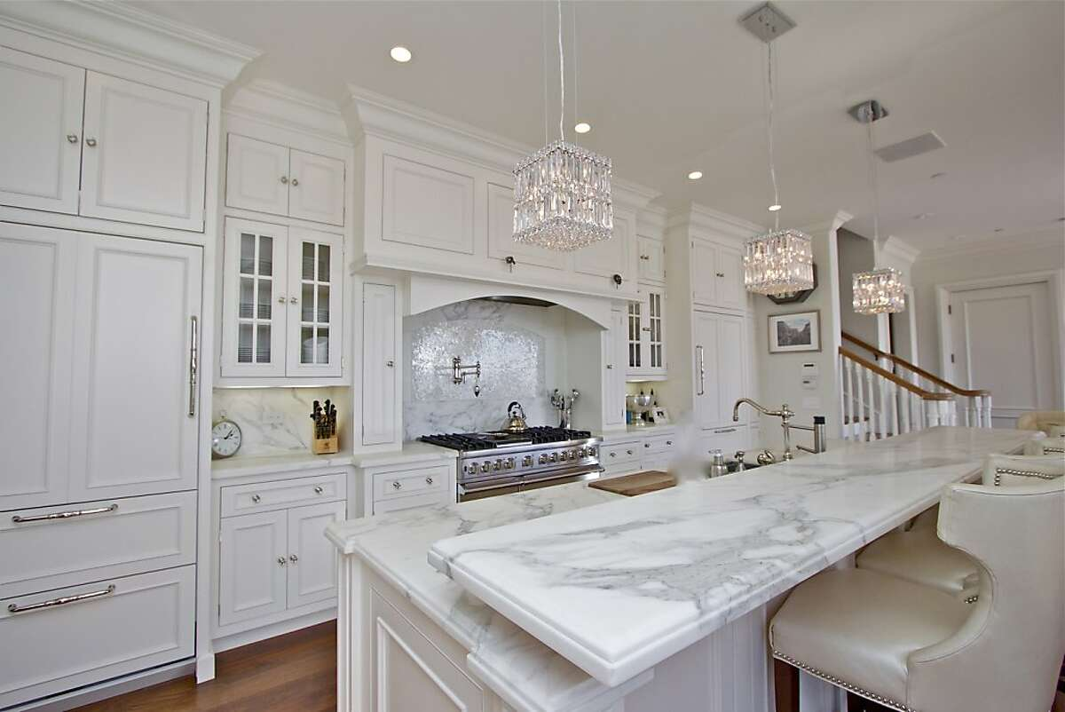 The kitchen includes a center island with marble counter and breakfast bar, along with stainless steel and wood-paneled appliances.