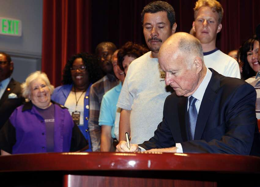 California Gov. Jerry Brown signs a bill to raise California minimum wage in Los Angeles, Sept. 2013. The earlier bill proposed an increase to $10 by 2016.