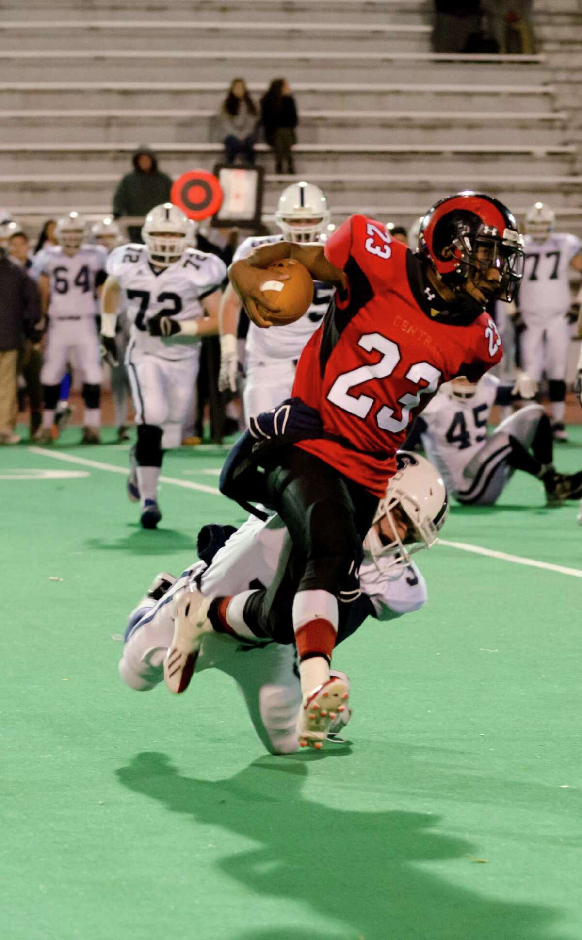 Central's quarterback Mykel Morris (23) carries the ball as Staples' Teddy Coogan (3) defends during the football game at Kennedy Stadium at Central High School in Bridgeport on Friday, Nov. 8, 2013