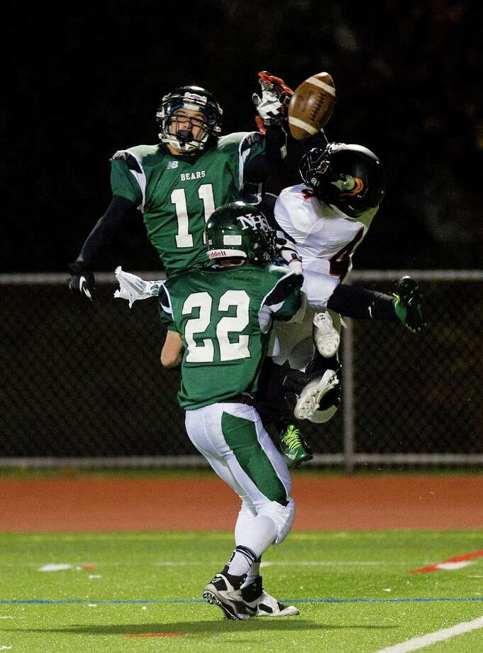 Norwalk's Yesid Rodriguez, left, Aaron Post, center, and Stamford's Jerry Aime all reach for a pass that fell incomplete during Friday's football game in Norwalk, Conn., on November 8, 2013. Photo: Lindsay Perry / Stamford Advocate