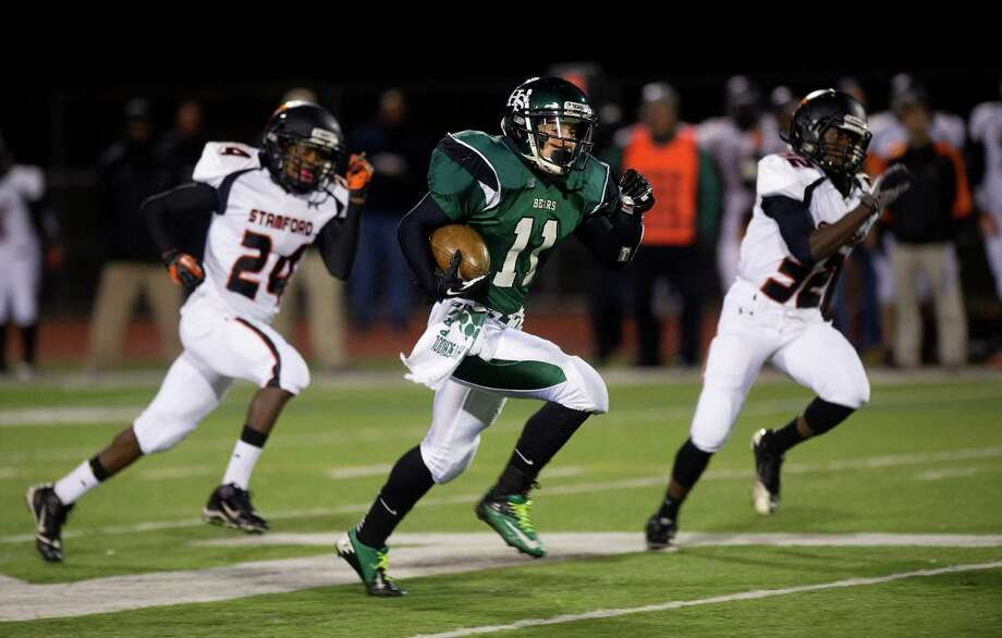 Norwalk's Yesid Rodriguez carries the ball during Friday's football game in Norwalk, Conn., on November 8, 2013. Photo: Lindsay Perry / Stamford Advocate