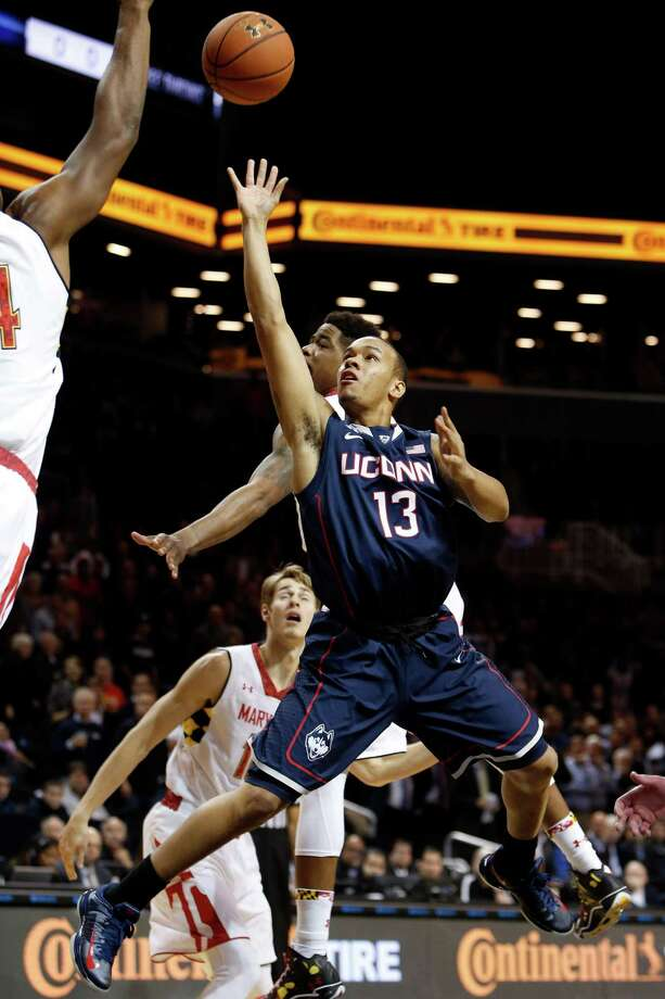 Connecticut's Shabazz Napier (13) shoots against Maryland's Shaquille Cleare, left, during the first half of an NCAA college basketball game Friday, Nov. 8, 2013, in New York. Photo: Jason DeCrow, AP / Associated Press