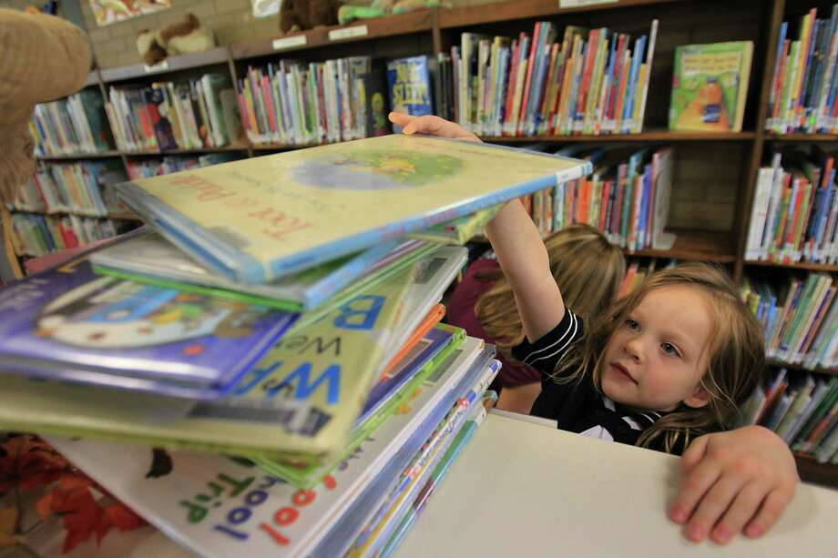 Sophie Peterson, 4, places a book on her checkout stack at the West University Library on Friday, a Harris County branch, one of many across the state at risk from further budget cuts by the federal Institute of Museum and Library Services. Photo: Mayra Beltran, Staff / © 2013 Houston Chronicle
