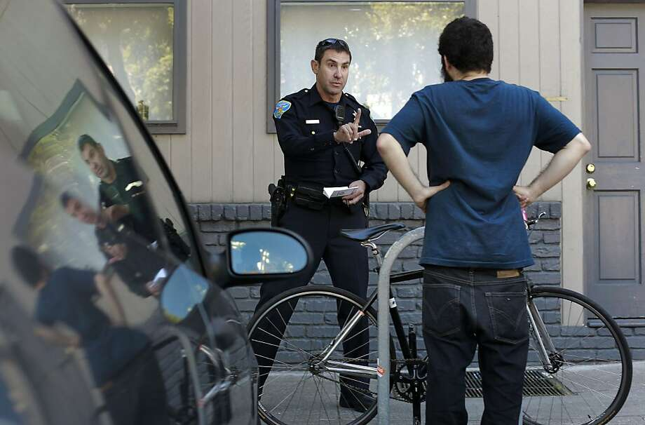 Luke Lucas, a San Francisco reserve police officer, talks with a bicyclist he stopped while on patrol. Photo: Michael Macor, The Chronicle