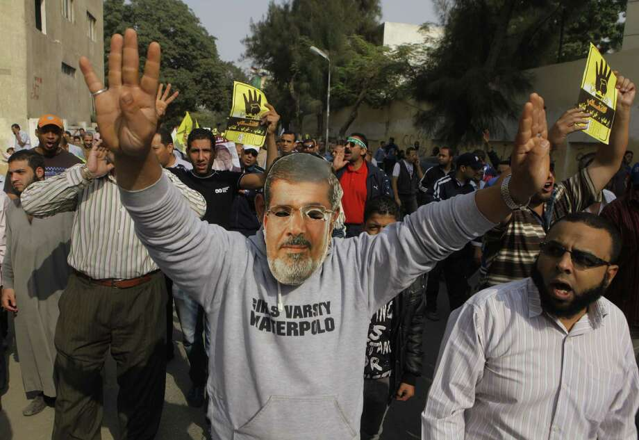 A supporter of ousted Egypt President Mohammed Morsi wears a mask bearing his picture during a protest Friday in Cairo. Morsi was ousted July 3. Photo: Amr Nabil / Associated Press