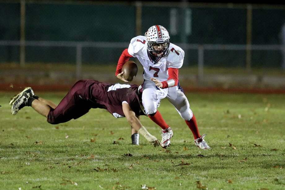 Foran High School's quarterback #7 Jake Kasuba escapes the tackle from a North Haven High School defender while rushing for yardage during Friday evening match up. Photo: Mike Ross / Mike Ross Connecticut Post freelance - @www.mikerossphoto.com