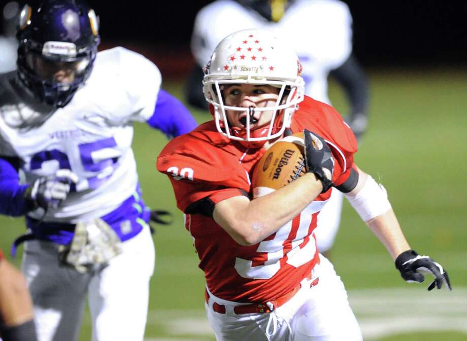 At right, Greenwich running back Thomas Rappa (# 30) gets past Zac Cowit (# 35) of Westhill during the high school football game between Greenwich High School and Westhill High School at Greenwich, Friday, Nov. 8, 2013. Photo: Bob Luckey / Greenwich Time