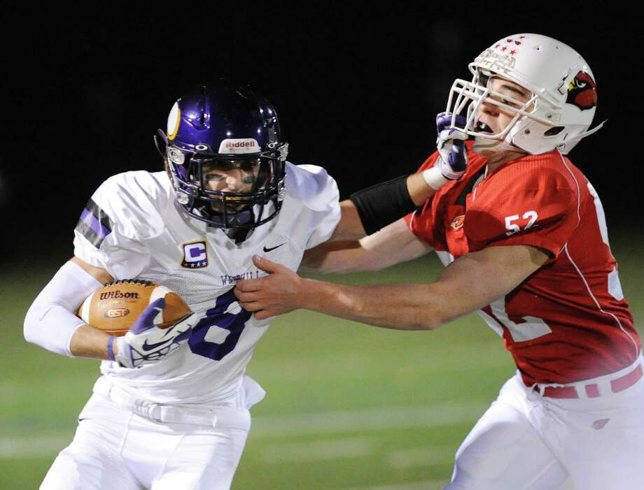 At left, Dante Fargnoli (# 8) of Westhill attempts to get around Justin Montier (# 52) of Greenwich on a running play during the high school football game between Greenwich High School and Westhill High School at Greenwich, Friday, Nov. 8, 2013. Photo: Bob Luckey / Greenwich Time