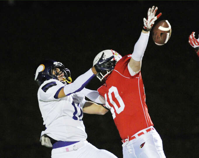 At right, Griffin Tiedy (# 40) of Greenwich breaks up a pass to Westhill receiver Evan Skoparantzos