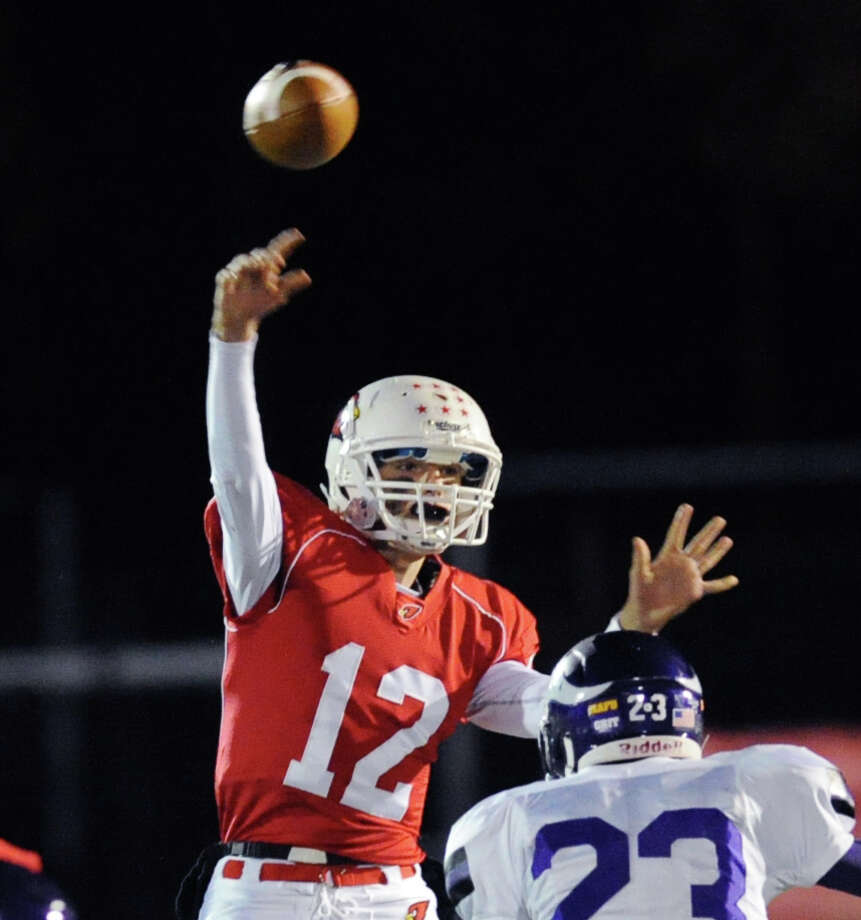 At left, Greenwich quarterback Matt Marzulla (# 12) throws while being pressured by Westhill's Jeff Glover (# 23) during the high school football game between Greenwich High School and Westhill High School at Greenwich, Friday, Nov. 8, 2013. Photo: Bob Luckey / Greenwich Time