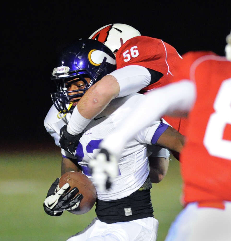 Westhill running back Tyreece Mitchell (# 22), left, is tackled by Jack Wynne (# 56) of Greenwich during the High school football game between Greenwich High School and Westhill High School at Greenwich, Friday, Nov. 8, 2013. Photo: Bob Luckey / Greenwich Time