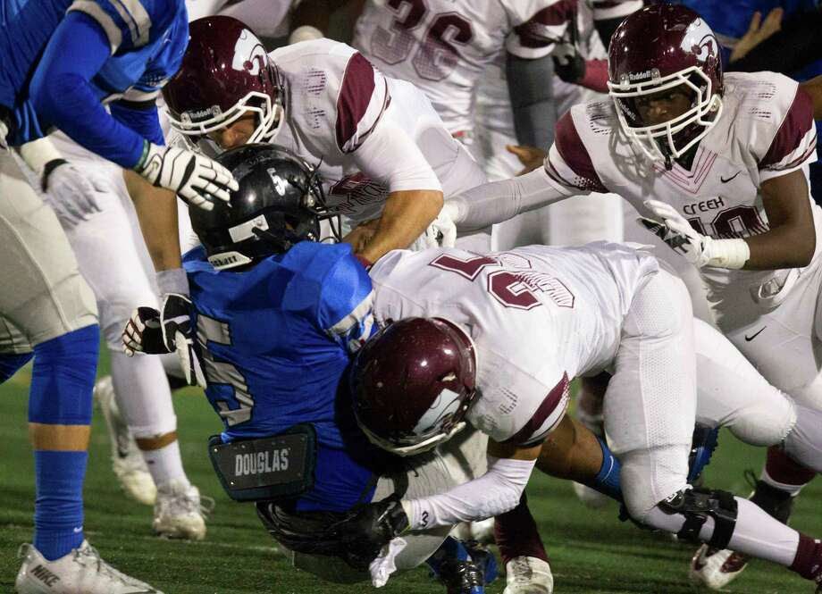 Clear Springs' Matt Guidry is tackled by a swarm of Clear Creek defenders during the first half of a high school football game at CCISD Veterans Stadium on Friday, Nov. 8, 2013, in League City. Photo: J. Patric Schneider, For The Chronicle / © 2013 Houston Chronicle