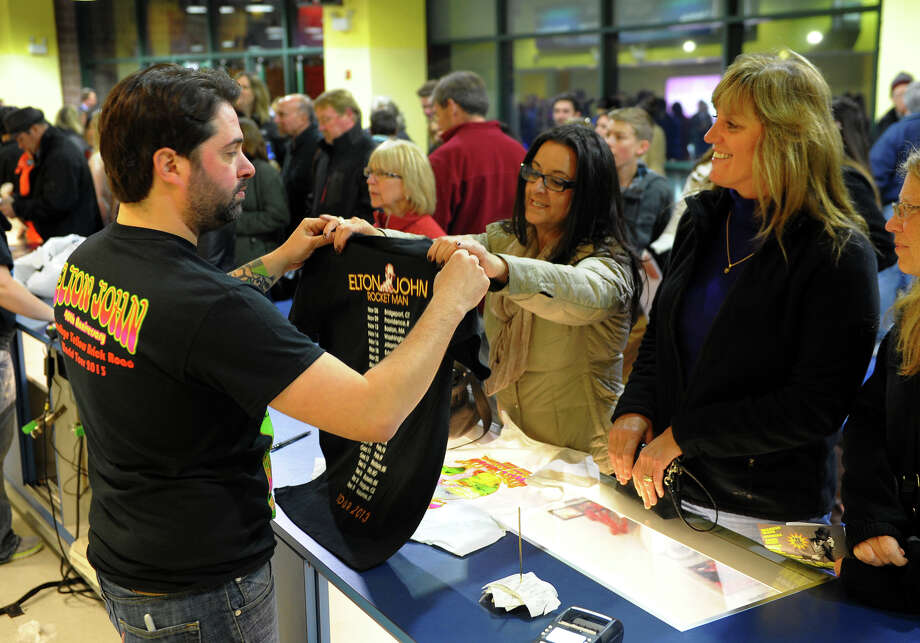 Peter Fertguena, with Statement, sells a T-shirt to Julie Dawid, of Easton, at the Sir Elton John concert at the Webster Bank Arena in downtown Bridgeport, Conn. on Friday November 8, 2013. Photo: Contributed Photo / Connecticut Post Contributed