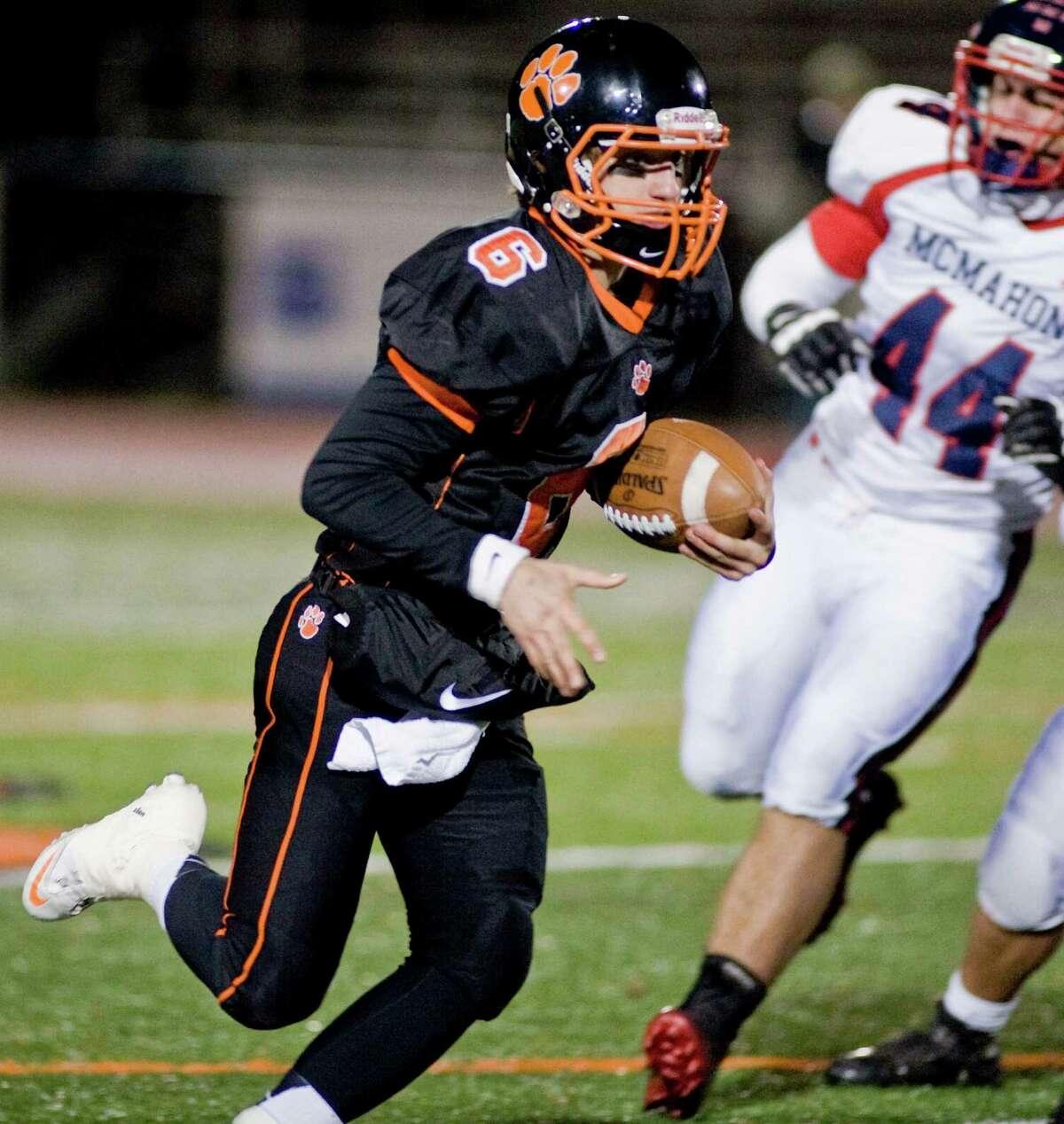 Ridgefield High School quarterback Ryan Dunn keeps the ball on a play against McMahon High School in the first quarter of a game at Ridgefield. Friday, Nov. 8, 2013