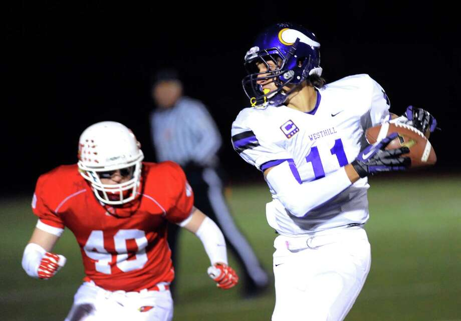 At left, Griffin Tiedy (# 40) of Greenwich goes to tackle Westhill receiver Evan Skoparantzos (# 11) during first quarter action of the high school football game between Greenwich High School and Westhill High School at Greenwich, Friday, Nov. 8, 2013. Photo: Bob Luckey / Greenwich Time