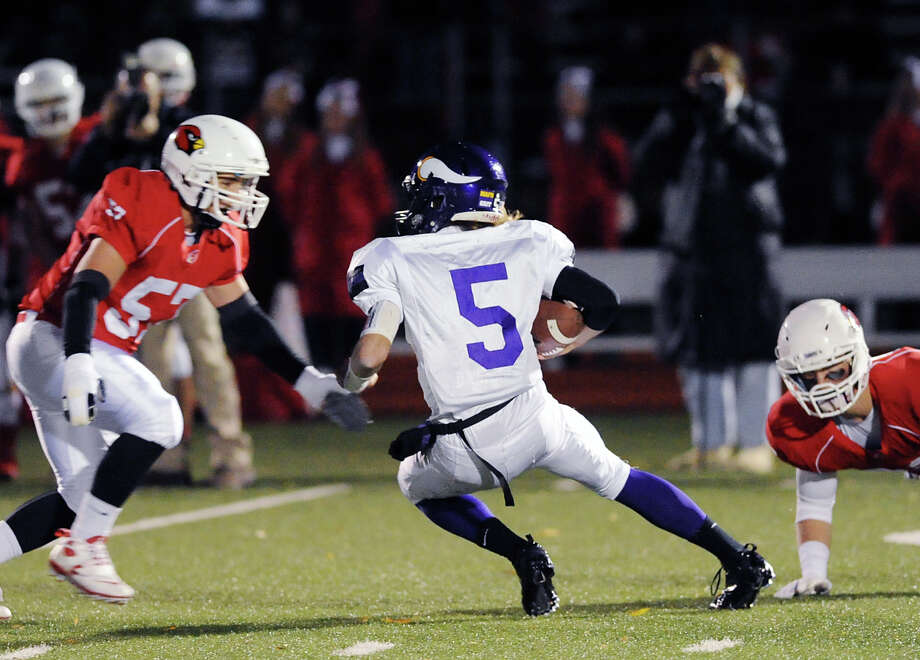 At left, Dom Colasacco (# 57) of Greenwich approaches Westhill quarterback Ryan Coppola (# 5) during the High school football game between Greenwich High School and Westhill High School at Greenwich, Friday, Nov. 8, 2013. Photo: Bob Luckey / Greenwich Time