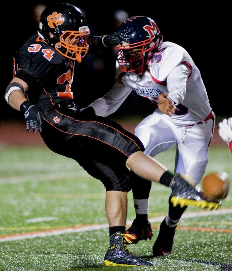 Ridgefield High School's Will Bonaparte gets off a punt before being hit by McMahon High School's Allan Lenard during a game at Ridgefield. Friday, Nov. 8, 2013 Photo: Scott Mullin / The News-Times Freelance