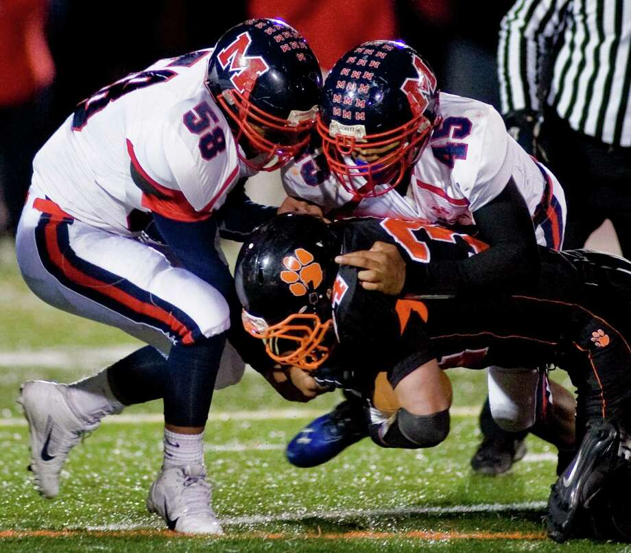 McMahon High School's Ryan Restivo, left, and Kenneth Keen team up on a tackle  in a game against Ridgefield High School, played at Ridgefield. Friday, Nov. 8, 2013 Photo: Scott Mullin / The News-Times Freelance