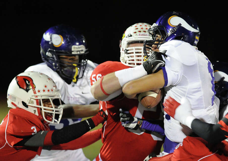 Greenwich defenders, Austin Longi, left, and Jack Wynne, at center, tackle a Westhill runner during the high school football game between Greenwich High School and Westhill High School at Greenwich, Friday, Nov. 8, 2013. Photo: Bob Luckey / Greenwich Time