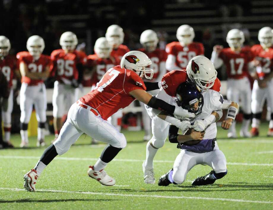 At left, Dom Colasacco (# 57) of Greenwich and teammate Jack Harrington (# 82), center, sack Westhill quarterback Ryan Coppola (# 5) during the High school football game between Greenwich High School and Westhill High School at Greenwich, Friday, Nov. 8, 2013. Photo: Bob Luckey / Greenwich Time
